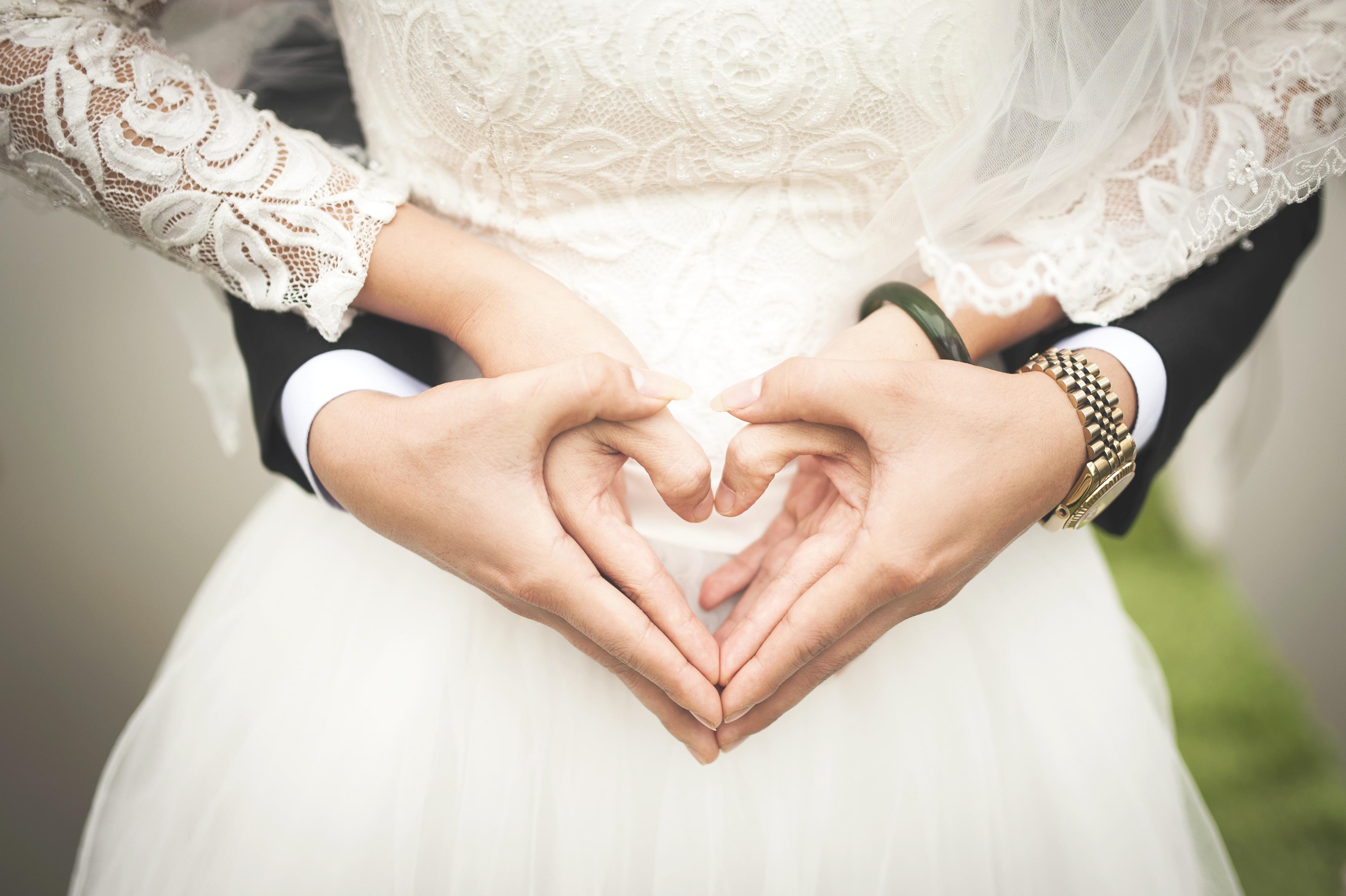 Die Hände eines Brautpaares formen ein Herz
