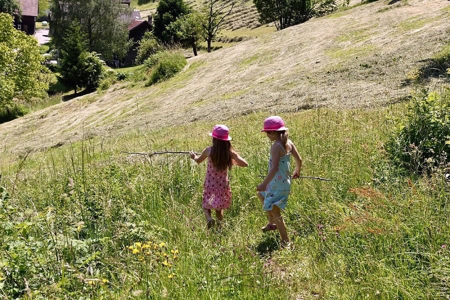 Zwei Mädchen laufen einen grünen Hügel hinab. Natur und Bewegung sorgen gemeinsam mit der richtigen Abwechslung für mehr Konzentration im Schulalltag.