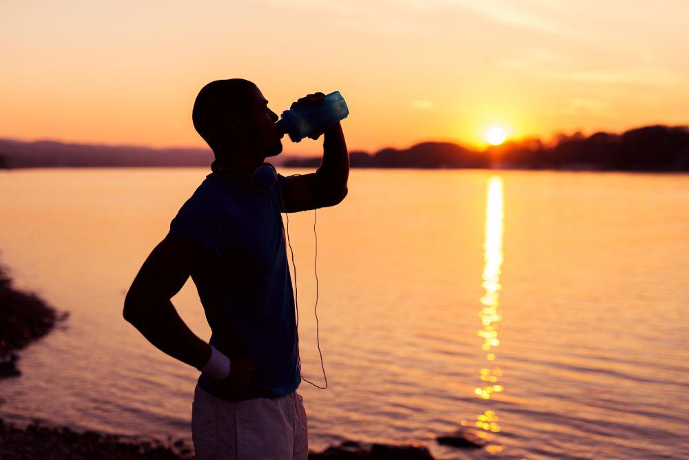 Sportlicher Mann trinkt bei Sonnenuntergang